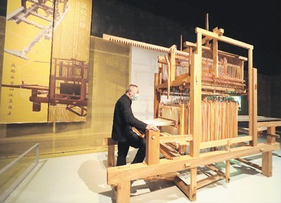工作人员在复原的汉代提花机上演示织锦。杜建坡摄