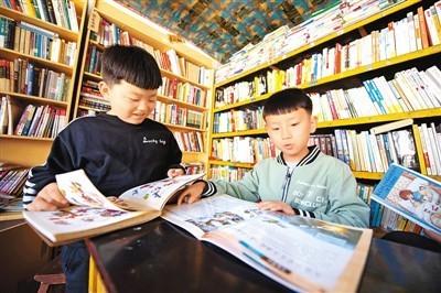 4月18日,小朋友在山西省大同市灵丘县东窖村大学蜂乡村图书馆内看书。  新华社记者 杨晨光摄