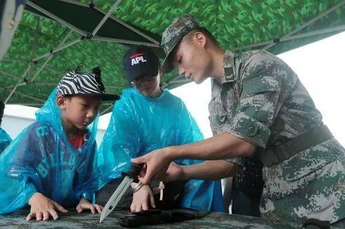 ▲资料图片:解放军驻港部队战士向市民讲解轻武器知识。(新华社)