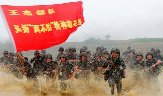 """△2015年6月25日,在一次对抗演习中,""""王杰班""""所在连队官兵发起冲锋。新华社发(赵聪摄)"""