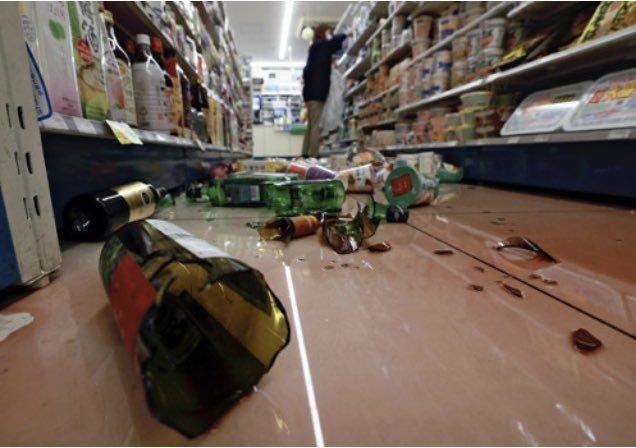 宫城县石卷市一家便利店在遭遇地震后,货架上的酒瓶砸落一地。图源:《读卖新闻》