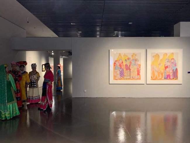 展览现场,马小娟的《高原红》与一旁身穿民族服饰的人