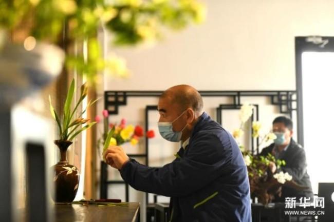 4月5日,燕赵插花艺人赵煜(前)在河北省石家庄市植物园插花艺术工作室创作。新华社发(陈其保 摄)