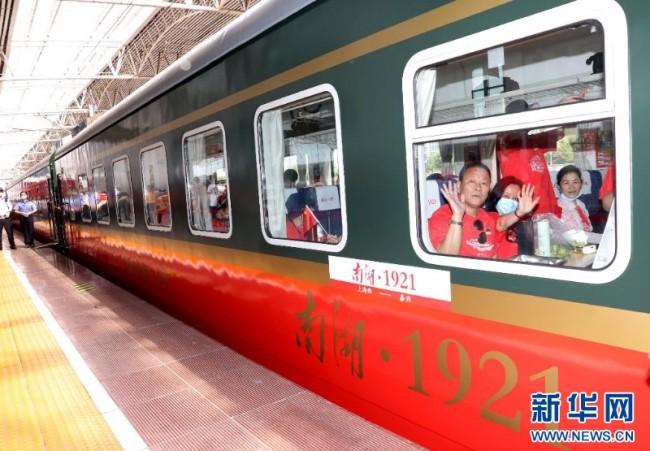 """2021年6月25日,乘坐Y701次""""上海至嘉兴红色旅游列车""""的旅客在铁路上海西站准备出发。这是一趟红色教育主题列车,连接起上海中共一大会址与嘉兴南湖。新华社记者 陈飞 摄"""