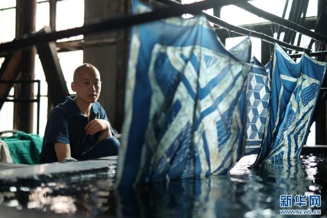 8月10日,在贵州省黔东南苗族侗族自治州丹寨县宁航蜡染工坊,成昊在查看蜡染时装面料的浸染效果。新华社发(黄晓海 摄)