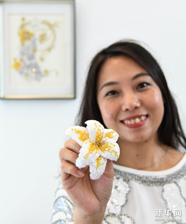 在广州荔湾区泮塘五约的法绣工坊,王颖峰展示她完成的法绣饰品(8月20日摄)。新华社记者 邓华 摄