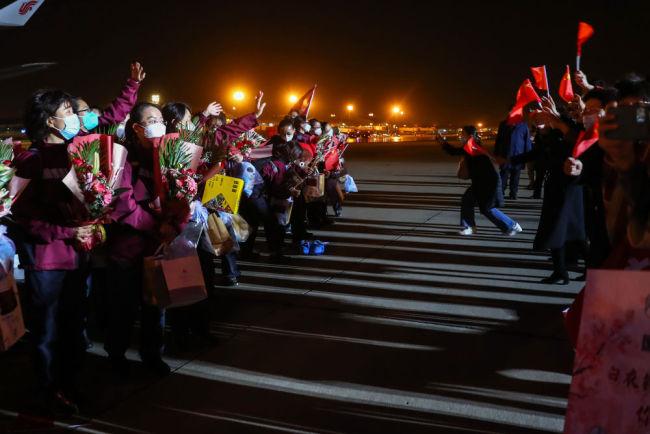 4月7日,国家援鄂医疗队队员抵达北京首都国际机场,与到场迎接的亲友相见,期待着14天隔离后的团聚。新华社记者 张玉薇 摄
