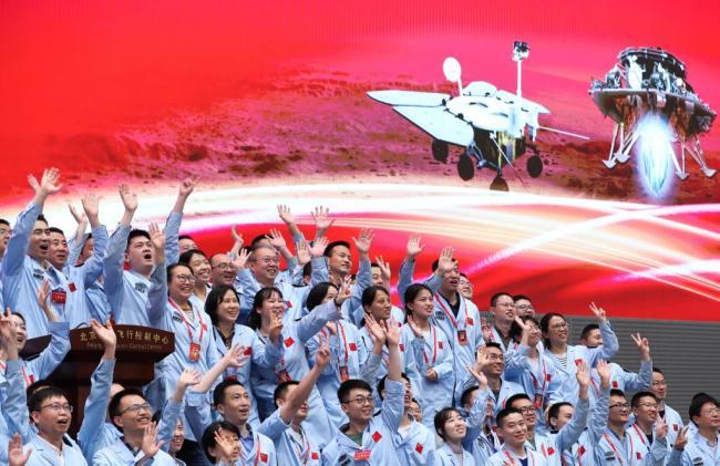 5月15日,航天科研人员在北京航天飞行控制中心指挥大厅庆祝我国首次火星探测任务着陆火星成功。新华社记者金立旺摄