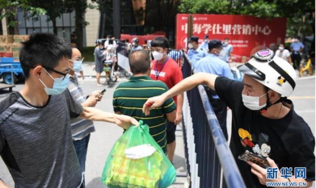 5月30日,在广钢新城封闭路口附近的网购货物线下集中配送点,市民(左)收取线上购买的鸡蛋。 新华社记者 邓华 摄