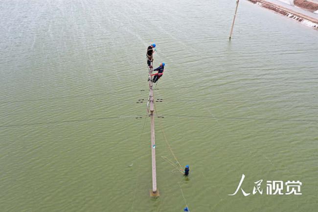 2021年7月12日,受强对流天气影响,山东省滨州市沿海地区遭遇龙卷风袭击,国网滨州供电公司的工作人员正在抢修电力设施。