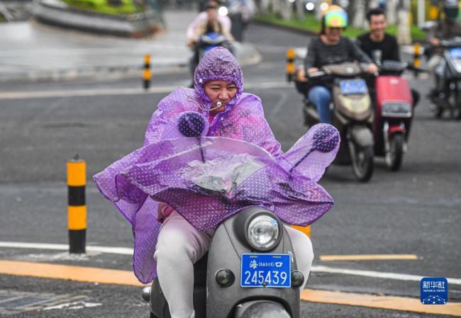 10月13日,市民迎风骑行在海口街头。