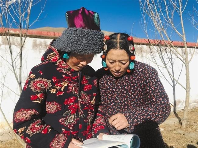 图为索县亚拉镇12村的措赤塔青与索吉在一起阅读新学的课文。