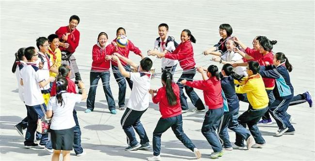 """图为西安市浐灞第一中学陕、藏学子们共同托起""""同心鼓""""。图片由西安市浐灞第一中学提供"""