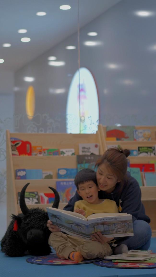 """图为在""""金宝贝拉萨中心"""",年轻的妈妈仁增旺沫正在陪儿子阅读绘本。"""
